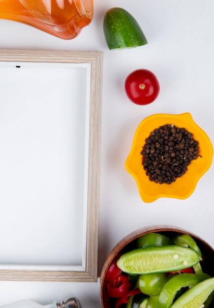 Draufsicht des gemüsesalats mit schwarzen pfeffersamen schneiden gurken-tomaten-geschmolzenes buttersalz und rahmen auf weißer oberfläche Kostenlose Fotos