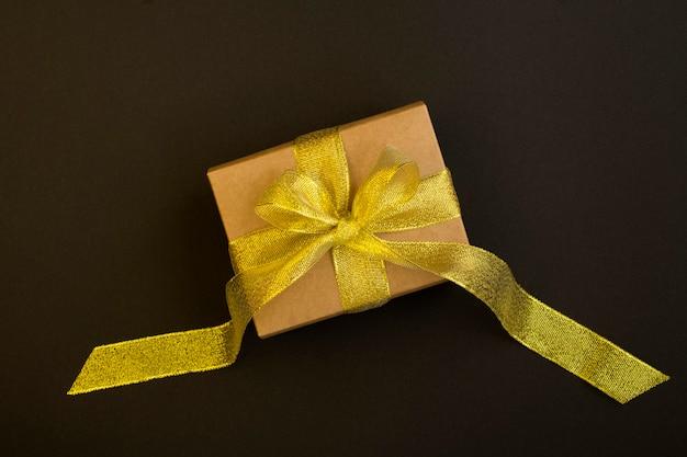 Draufsicht des geschenks mit goldschleife auf der schwarzen oberfläche Premium Fotos
