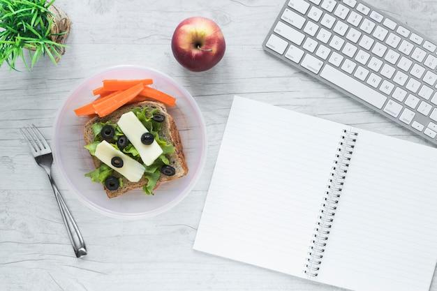 Draufsicht des gesunden lebensmittels mit geöffnetem gewundenem buch und drahtloser computertastatur auf tabelle Kostenlose Fotos