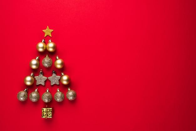 Draufsicht des goldenen balls und des sternes in form des weihnachtsbaums auf rotem hintergrund. Premium Fotos