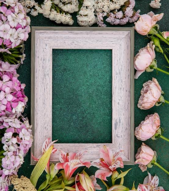 Draufsicht des grauen rahmens mit hellrosa blumen auf einer grünen oberfläche Kostenlose Fotos