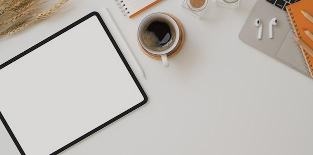 Draufsicht des herbstarbeitsplatzes mit tablette des leeren bildschirms, kaffeetasse und büroartikel Premium Fotos