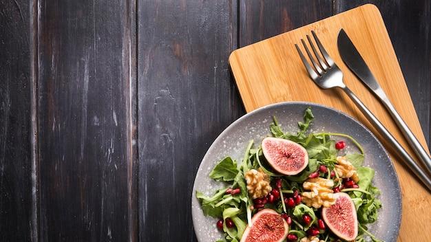Draufsicht des herbstfeigen-salats auf teller mit besteck und kopierraum Kostenlose Fotos