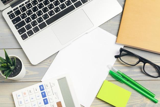 Draufsicht des hölzernen desktops mit gläsern und briefpapierartikeln nah oben. attrappe, lehrmodell, simulation Premium Fotos