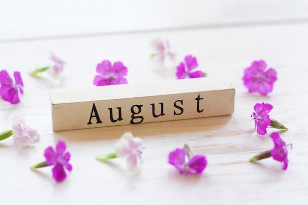 Draufsicht des hölzernen kalenders mit august-zeichen und rosa blumen. Premium Fotos