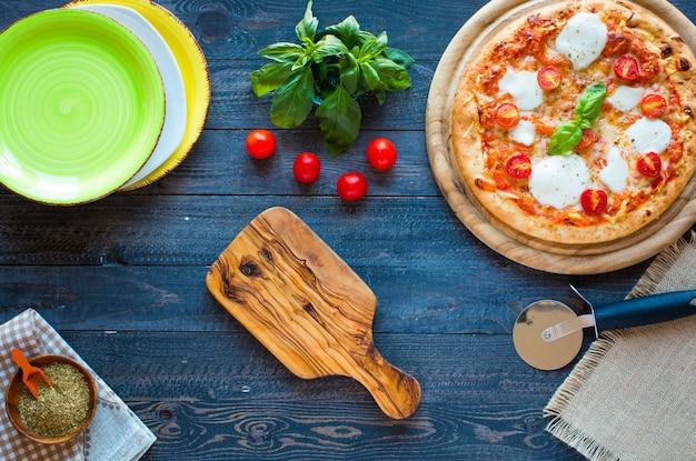 Draufsicht des italienischen klassischen pizza margherita über einem holztisch mit belägen Premium Fotos