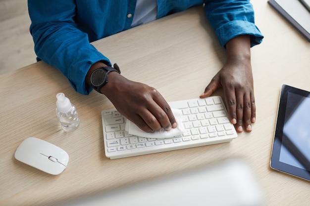 Draufsicht des jungen afroamerikanischen mannes, der tastatur mit desinfektionstüchern während der arbeit am schreibtisch im postpandemiebüro abwischt Premium Fotos