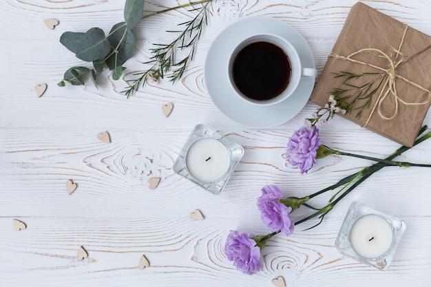 Draufsicht des kaffees, geschenk, kerzen, blumen auf weißem holztisch. Premium Fotos