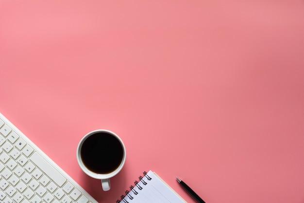 Draufsicht des kaffees mit notizbuch und anderen versorgungen auf rosa hintergrund und copyspace Premium Fotos