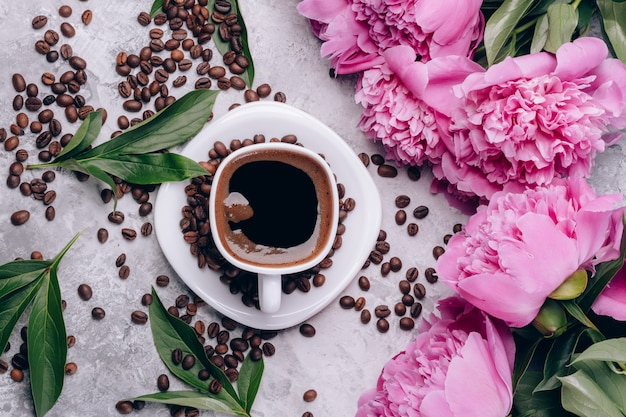 Draufsicht des kaffees und der pfingstrosen auf einem tisch mit kaffeebohnen Premium Fotos