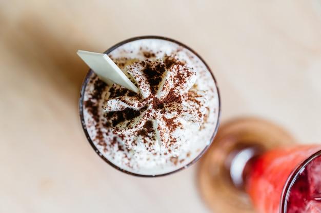 Draufsicht des karamellmilchshakenbelags mit peitschecreme und schokoladenpulver. Premium Fotos