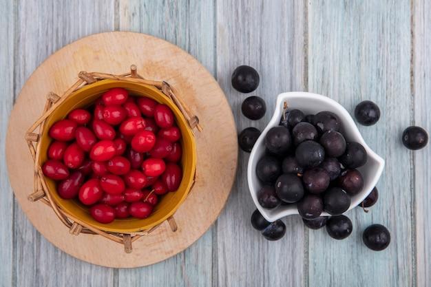 Draufsicht des kleinen dunkelvioletten schwarzdorns auf einer weißen schüssel mit roten kornelkirschenbeeren auf einem eimer auf einem hölzernen küchenbrett auf einem grauen hölzernen hintergrund Kostenlose Fotos