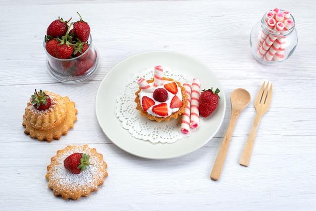 Draufsicht des kleinen kuchens mit sahne und geschnittenen erdbeerkuchen-bonbons auf weißem, süßem obstkuchen-beerenzucker Kostenlose Fotos