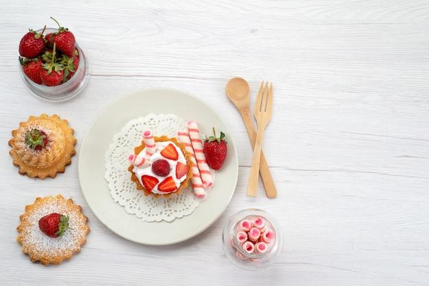 Draufsicht des kleinen kuchens mit sahne und geschnittenen erdbeerkuchen-bonbons auf weißem süßem zucker des obstkuchens Kostenlose Fotos
