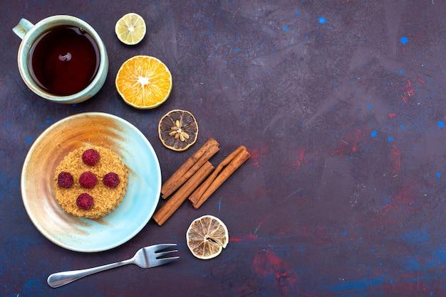 Draufsicht des kleinen runden kuchens mit frischen himbeeren innerhalb platte mit tee auf der dunkelblauen oberfläche Kostenlose Fotos