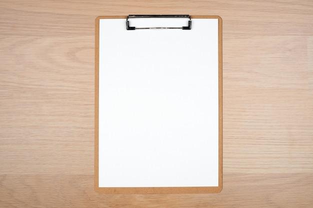 Draufsicht des klemmbrettes mit weißem blatt auf braunem hölzernem hintergrund Premium Fotos