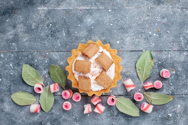 Draufsicht des köstlichen cremigen kuchens mit plätzchen zusammen mit geschnittenen rosa bonbons auf grauer, kuchensüßer backcreme Kostenlose Fotos