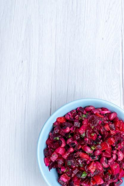 Draufsicht des köstlichen rübensalats, der mit gemüse und gemüse in der blauen platte auf hellem schreibtisch geschnitten wird, gemüsesalat der gemüsevitamin-lebensmittelmahlzeit Kostenlose Fotos