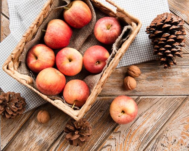 Draufsicht des korbes der äpfel mit kiefernkegeln Kostenlose Fotos