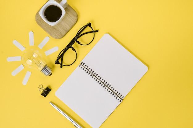 Draufsicht des kreativen flachen lagekonzeptes des arbeitsplatzschreibtischs redete designbüroartikel mit stift, notizblock, brillen an Premium Fotos