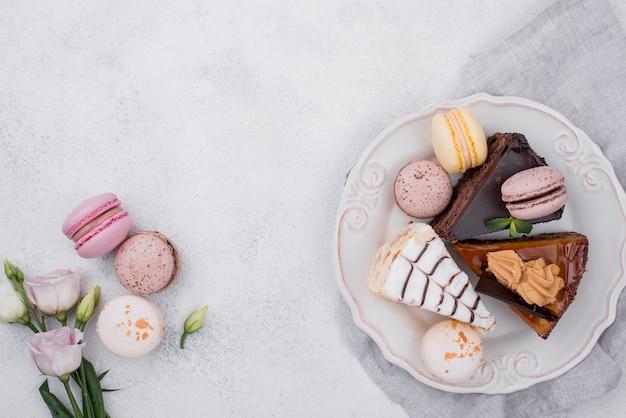 Draufsicht des kuchens auf teller mit macarons und rose Kostenlose Fotos
