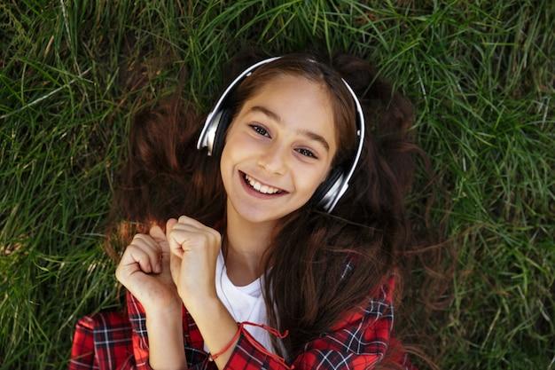 Draufsicht des lächelnden jungen brünetten mädchens, das auf gras liegt Kostenlose Fotos