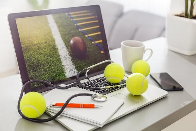 Draufsicht des laptops, sportausrüstung, tennisball, sportverwaltungsweißtabelle. Premium Fotos