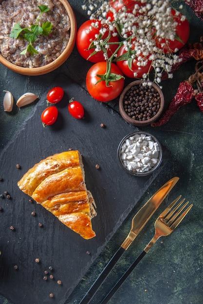 Draufsicht des leckeren fleischpastetenstücks mit roten tomaten und gefülltem fleisch auf dunkler oberfläche Kostenlose Fotos