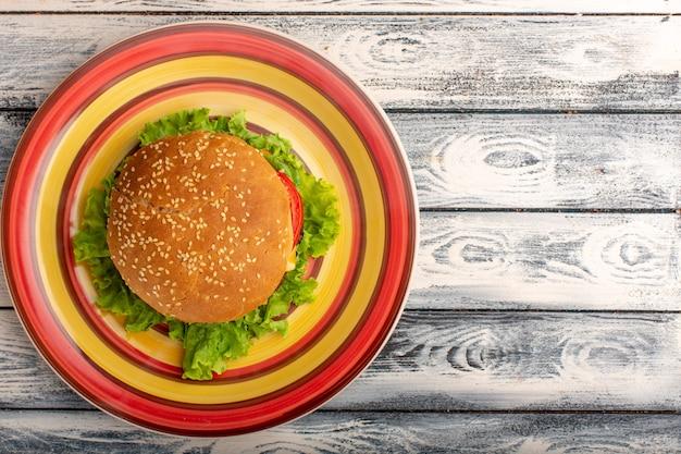 Draufsicht des leckeren hühnchensandwiches mit grünem salat und gemüse innerhalb der farbigen platte auf rustikaler grauer oberfläche Kostenlose Fotos