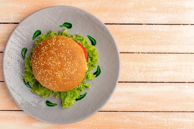 Draufsicht des leckeren hühnchensandwiches mit grünem salat und gemüse innerhalb platte auf der hölzernen rustikalen cremeoberfläche Kostenlose Fotos