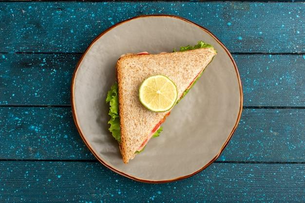 Draufsicht des leckeren sandwichs mit grünen salattomaten auf dem blauen schreibtisch Kostenlose Fotos