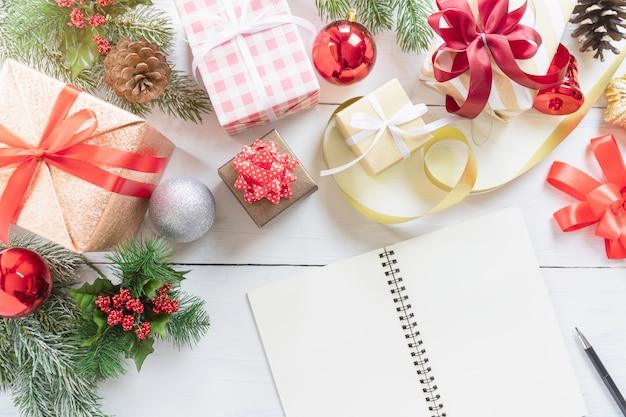 Draufsicht des leeren notizbuches, des bleistifts und der dekorativen weihnachts- oder neujahrsfeiertaggeschenkbox Premium Fotos
