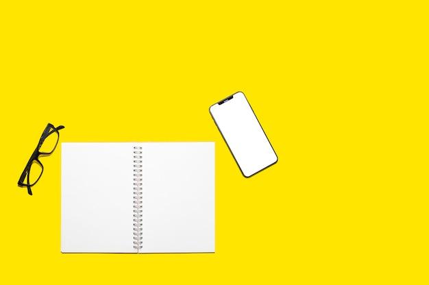 Draufsicht des leeren notizbuchpapiers und des smartphoneschirms Premium Fotos