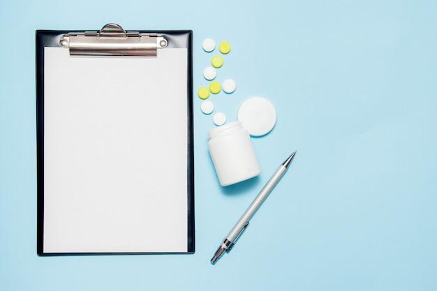 Draufsicht des leeren papiers für das schreiben von doktorverordnung. pillen auf blau Premium Fotos