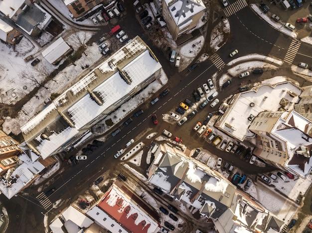 Draufsicht des luftschwarzweiss-winters der modernen stadt mit hohen gebäuden, geparkten und beweglichen autos entlang straßen mit fahrbahnmarkierung. Premium Fotos
