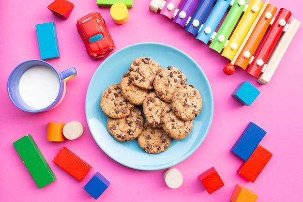 Draufsicht des lustigen kinderfrühstücks mit milch- und keksplätzchen, begleitet von spielzeug und farbigem xylophon auf rosa hintergrund Premium Fotos