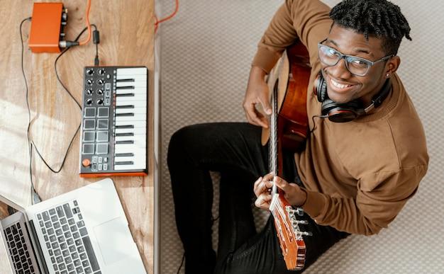Draufsicht des männlichen smiley-musikers zu hause, der gitarre spielt und mit laptop mischt Kostenlose Fotos