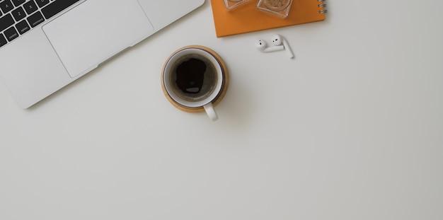 Draufsicht des minimalen arbeitsplatzes mit laptop-computer, einem tasse kaffee und büroartikeln Premium Fotos