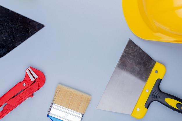Draufsicht des musters vom satz der bauwerkzeuge als rohrschlüssel-sicherheitshelmkellen-pinsel und spachtel auf grauem hintergrund Kostenlose Fotos