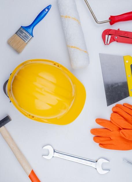 Draufsicht des musters vom satz von bauwerkzeugen als backsteinhammerrohrschlüssel-sicherheitshelm-spachtelmesser-schmerzkontrollpinsel und gabelschlüssel auf weißem hintergrund Kostenlose Fotos