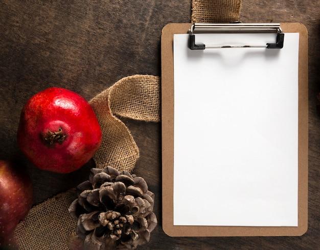 Draufsicht des notizblocks mit herbstlichem granatapfel und tannenzapfen Kostenlose Fotos