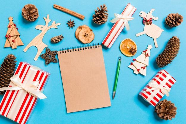 Draufsicht des notizbuches auf dem blau gemacht von den weihnachtsdekorationen. Premium Fotos