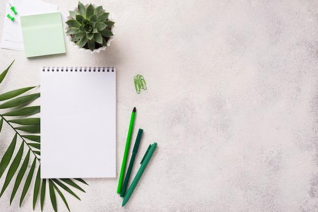 Draufsicht des notizbuches auf schreibtisch mit saftiger anlage und blättern Kostenlose Fotos
