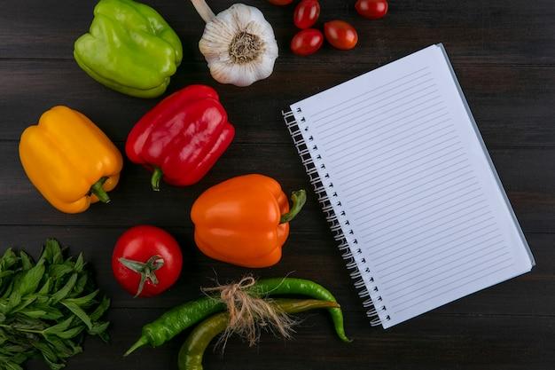Draufsicht des notizbuchs mit farbigem paprika-chilischoten-knoblauchbündel von minze und von tomaten auf einer holzoberfläche Kostenlose Fotos