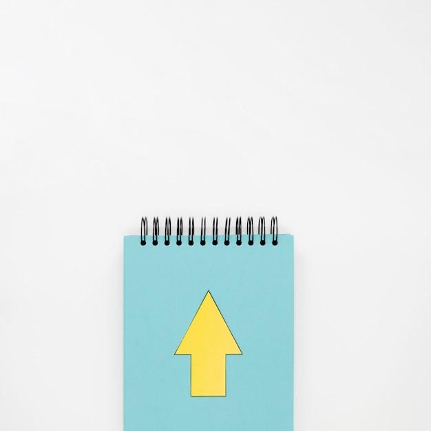 Draufsicht des notizbuchs mit gelbem pfeil Kostenlose Fotos