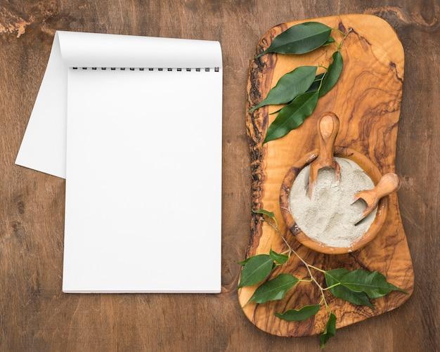 Draufsicht des notizbuchs mit schüssel des pulvers und der schaufeln Kostenlose Fotos