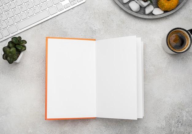 Draufsicht des offenen gebundenen buches auf schreibtisch mit kaffee Kostenlose Fotos