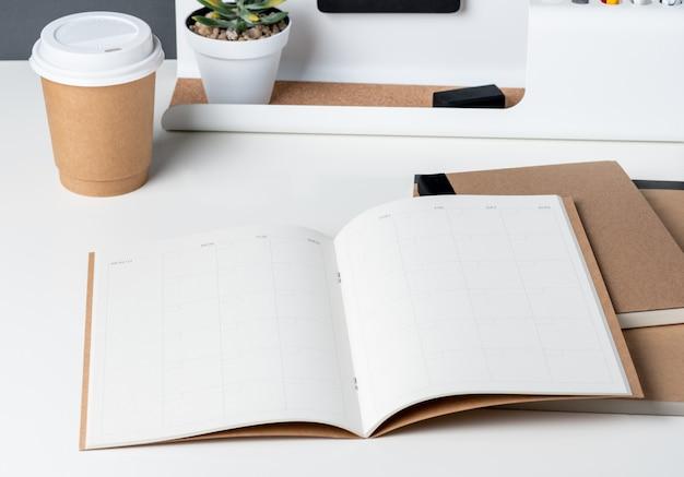 Draufsicht des offenen kalenderplaners mit modernem büromaterial Premium Fotos