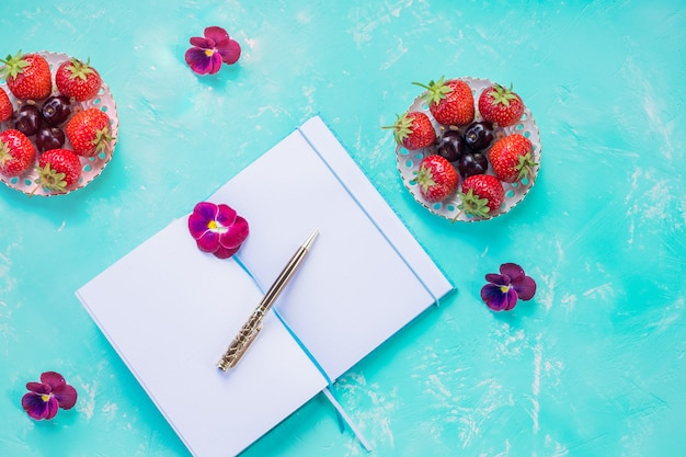 Draufsicht des offenen leeren notizbuchs, verspotten über blaue schreibtischwand. wildbeerenfrucht-arrangement. erdbeeren, konzept des geschäftigen morgenfrühstücks, sommer-listenplaner. Premium Fotos