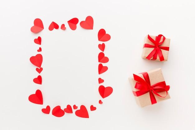 Draufsicht des papierherzrahmens mit geschenken Kostenlose Fotos